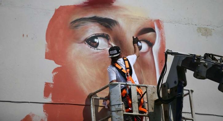Venezuela'dan geldi, öğrenciler okula gitsin diye duvar boyadı...